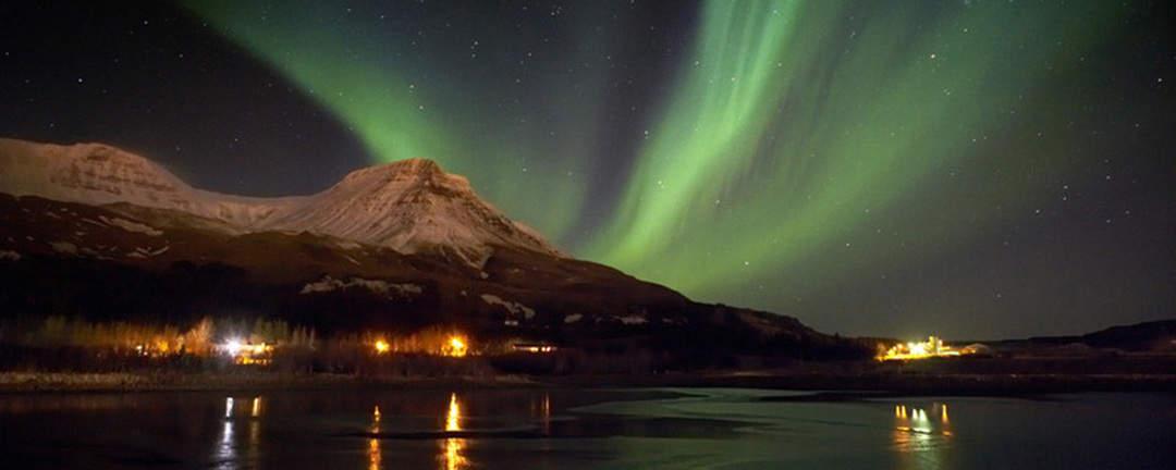 Norrsken som dansar på den kolsvarta natthimlen på Island