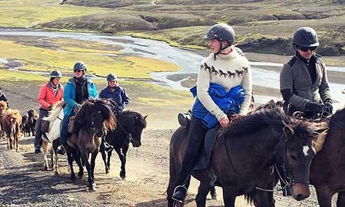 Ridsällskap rider med Riding Iceland uppför kulle med vackra vyer på Island